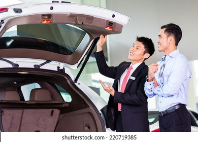 Car salesman in Asian dealership showing trunk of SUV car to customer