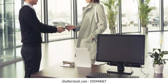car salesman handing over car key to customer in car showroom