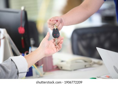 Car salesman handing over the keys for a new car to a businessman