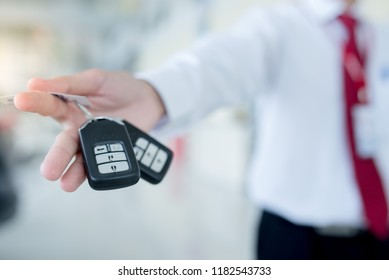 car salesman handing over your new car keys, dealership and sales concept