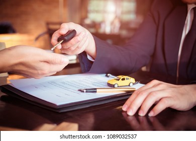 Car salesman holding key to his client after signing contract,concept for sale car,insurance with car, moving car or renting car