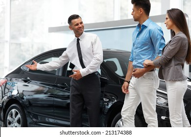 Car Salesman Invites Customers at Showroom.