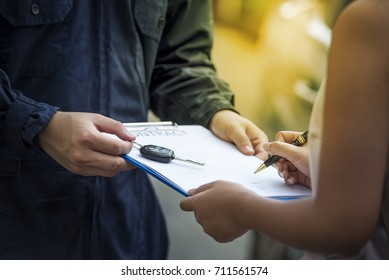 car salesman is making deal with lender. Used cars cheaper than new cars. But to buy a used car, the car must be thoroughly examined. Before lender signing deal leasing, the contract must be cautious.