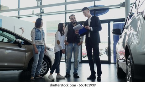 Car salesman shows a young family information about their new car.