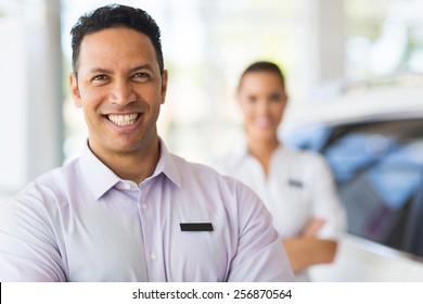 car salesman standing in front of colleague in showroom