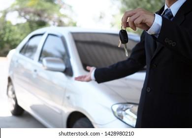 Car salesmen and keys presenting car trading