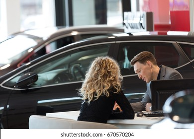 Car salesperson discussing with female customer while sitting in showroom