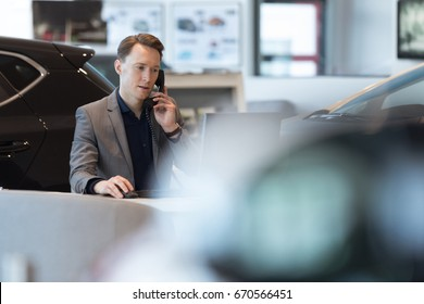 Car salesperson talking on landline phone while working in showroom
