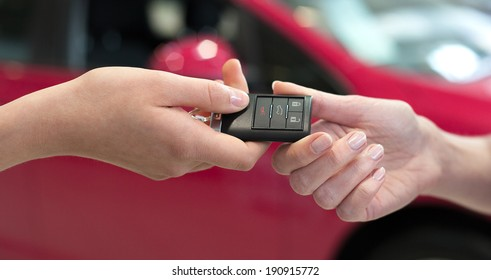 Car saleswoman handing over the keys for a new car to a young woman
