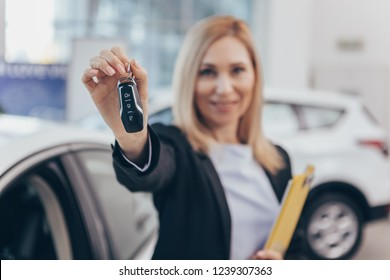 Car saleswoman smiling cheerfully, holding out car key to the camera, standing in front of new cars for sale. Selective focus on car keys in the hands of a female car dealer. Offer, discount concept