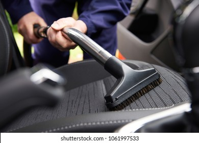 Car seat vacuum, car detailing and cleaning of interior seats at luxury modern cars.