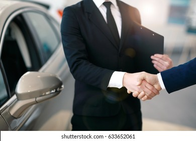 Car seller and client handshake at car dealership.