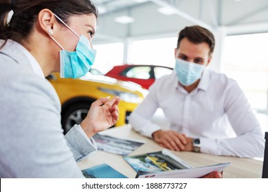 Car seller and customer sitting at the table in car salon and talking about specifications and car performances during corona virus. They both have face masks on.