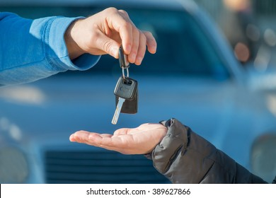 car seller gives the keys to new automobile owner or car rental customer gets the keys  -  rent-a-car or vehicle ownership concept