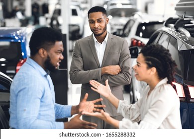 Car Seller Looking At Afro Couple Having Quarrel About Buying Too Expensive Car Standing In Dealership Showroom. Selective Focus