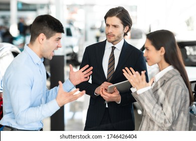 Car Seller Looking At Couple Having Quarrel About Buying Too Expensive Car In Dealership Showroom. Selective Focus