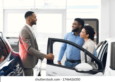 Car Seller Man Consulting Buyers Showing Luxury Auto In Dealership Shop. Car Sales Concept