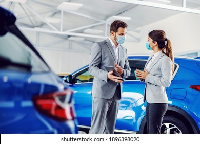 Car seller standing in car salon with a customer and showing on tablet car performances and specifications. They both have face masks on faces because it's corona outbreak.
