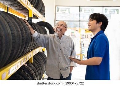 Car service. Asian salesman recommend new tire wheel on shelves shelf to senior elderly customer at the auto car repair shop. Specialist mechanic and customer examining new tire wheel