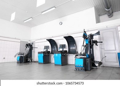 Car service center interior with modern tire fitting and wheel balancing equipment