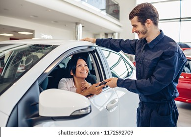 Car service center scene. The mechanic giving car key to the client