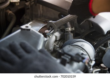 Car service ,fitting a car engine with wrench