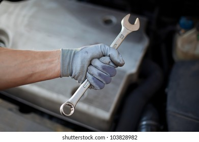 Car service. Hand holding wrench.