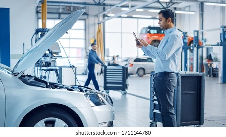 Car Service Manager Uses a Tablet Computer with an Augmented Reality Diagnostics Software. Specialist Inspecting the Car in Order to Find Broken Components Inside the Engine Bay.