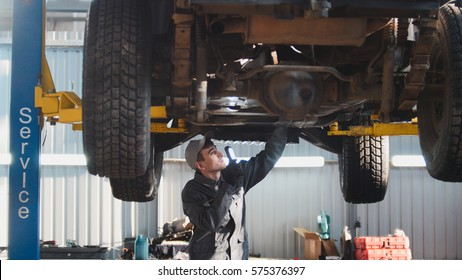Car service - a mechanic checks the suspension of SUV, wide angle