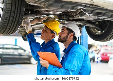 Car service mechanic repairing and maintenance a lifted checks the suspension Car repair and maintenance concept at car service center