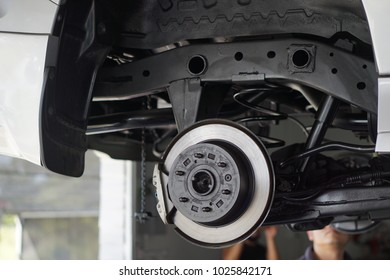 Car service - mechanic unscrewing automobile parts while working under a lifted auto.Disc car close up