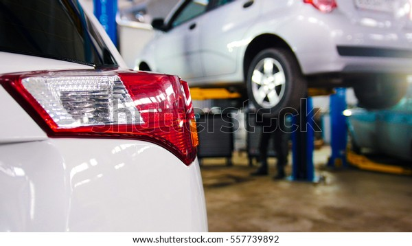 Car service - red backlights of white auto in opposite  lifted automobile