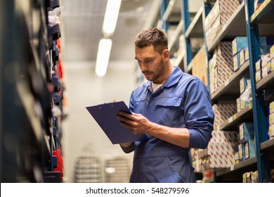 car service, repair, maintenance and people concept - auto mechanic man or smith writing to clipboard at workshop or warehouse