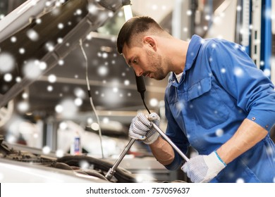 car service, repair, maintenance and people concept - auto mechanic man with wrench and lamp working at workshop over snow