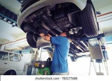 Car service, repair & maintenance. Professional car mechanic man working under lifted car in auto repair service.