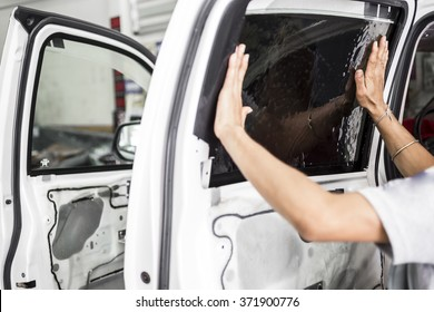 Car service station. Closeup image of a car mechanic man attaching tinting film foil to car window in specialized service station