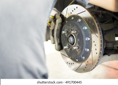 Car Service and technician concept - Front disc brake on maintenance and fix by asian technician disk brake service man with copyspace