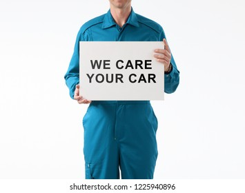Car service technician holds white card with text.