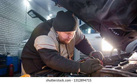 Car service. Thick mechanic man checks the voltage with a multimeter inside the car