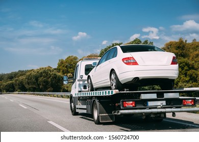 Car Service Transportation Concept. Tow Truck Transporting Car On Motorway Freeway Highway. Help On Road Transports Wrecker Broken Car. Transportation Faults And Emergency Cars.
