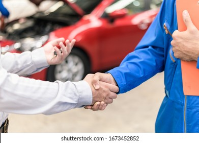 Car service, vehicle repair concept : Car service technician shaking hands with vehicle owner customer after sending car for repairing or check at automobile service center.