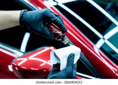 Car service worker applying nano coating on a car detail.