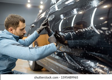 Car service worker sticking anti-gravel film on a car body with scrapper at the detailing vehicle workshop. Concept of car body protection with special films