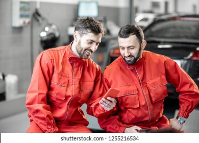 Car service workers in red uniform having a break sitting together with phone on the wheels at the tire mounting service