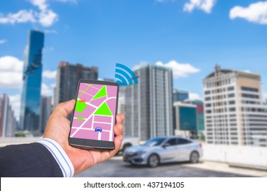 Car sharing concept. Sharing economy and collaborative consumption. Hand hold smart phone with map application on screen against car parking area background.