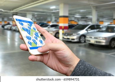 Car sharing , pick me up , auto drive and internet of things in smart car concept. Hand holding smart phone and application dashboard with blur car parking background.