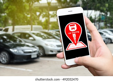 Car sharing service or rental concept. Sharing economy and collaborative consumption. Customer hand holding smart phone with icons application screen and blur cars background.