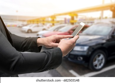 Car sharing service or rental concept. Sharing economy and collaborative consumption. Customer man suit hand using smart phone with blur cars background with fare light effect.