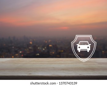 Car with shield flat icon on wooden table over blur of cityscape on warm light sundown, Business automobile insurance concept