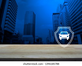 Car with shield flat icon on wooden table over modern office city tower and skyscraper, Business automobile insurance concept